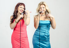 Two Girls actress singer in cocktail dresses with microphones blonde and brown hair Stock Photos