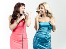 Two Girls actress singer in cocktail dresses with microphones blonde and brown hair Stock Photography