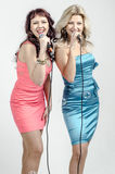 Two Girls actress singer in cocktail dresses with microphones blonde and brown hair Royalty Free Stock Photography