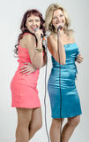 Two Girls actress singer in cocktail dresses with microphones blonde and brown hair Royalty Free Stock Image