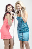 Two Girls actress singer in cocktail dresses with microphones blonde and brown hair Royalty Free Stock Photo