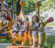 Two girls with admiration go for a drive on the carousel Royalty Free Stock Image