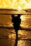 Two girls in affectionate silhouette. Two girls in silhouette against a golden sunset one holding up the over with affection Stock Photo