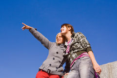 Two girls against blue sky. Two young smiling girls against blue sky Stock Photography