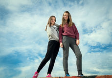 Two girls against the sky. Two beautiful young girls were photographed against the sky Royalty Free Stock Photo