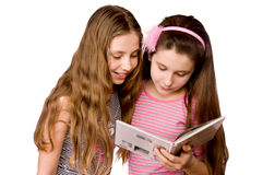 Two girls in the age of ten and eleven reading Royalty Free Stock Image