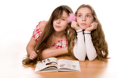 Two girls in the age of ten and eleven reading. Book on the floor on white Royalty Free Stock Image