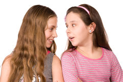 Two girls in the age of ten and eleven talking. Isolated on white Royalty Free Stock Image