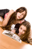 Two girls in the age of ten reading book. Two girls in the age of ten and eleven reading book on the floor on white Stock Image