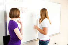 Two Girls in Algebra Class. Two high school girls in algebra class, working equations on the board stock photography