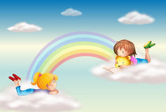 Two girls along the rainbow Royalty Free Stock Image