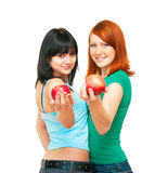 Two girls with apples. The image of two girls stretching apples Stock Image
