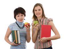 Two girls with apples and books; isolated on white Stock Images