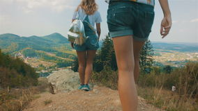 Two girls approach the cliff and enjoy the view of the mountains. Two happy, beautiful and fashionable girl approach the cliff and enjoy the beautiful view of stock video footage