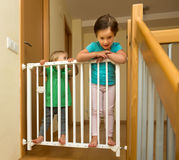 Two  girls approaching safety gate of  stairs Royalty Free Stock Photo
