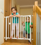 Two girls approaching safety gate of  stairs Stock Photos