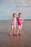Two girls (4-5) with arms around each other on beach Royalty Free Stock Photos