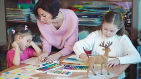 Two girls in art class with teacher stock footage