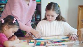 Two girls in art class with teacher. Medium shot stock video