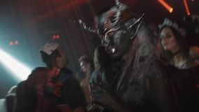 Two girls as devil characters dance in crowd at night club halloween party stock footage