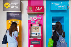 Two girls at ATM in Thailand Stock Photography