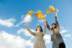 Two girls and Autumn leaves. Two happy student girls celebrates autumn by throwing up yellow leafage over blue sky Royalty Free Stock Photos