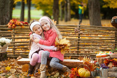 Two girls in autumn park sitting on wooden bench near a fence Royalty Free Stock Image