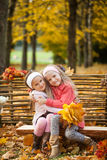 Two girls in autumn park sitting on wooden bench near a fence Stock Photos
