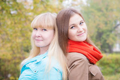 Two girls are in autumn park Stock Images