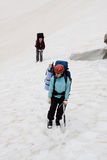 Two girls backpackers on snow. Royalty Free Stock Photos