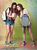 Two girls with backpacks looking in the box. Beautiful young women in shorts and with backpacks looking at a box stock photos
