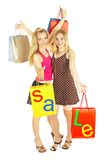Two girls with bags - comparison shopping. Sale! Royalty Free Stock Photo