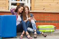 Two girls with bags reading text message while sitting at the station. Cute girlfriend,two young women-a brunette with long straight hair,cute smile,dressed in Stock Photography