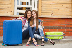 Two girls with bags reading text message while sitting at the station. Cute girlfriend,two young women-a brunette with long straight hair,cute smile,dressed in Royalty Free Stock Images