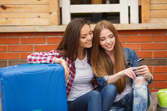 Two girls with bags reading text message while sitting at the station. Cute girlfriend,two young women-a brunette with long straight hair,cute smile,dressed in Royalty Free Stock Photos
