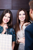 Two girls speak to shop assistant Stock Photo
