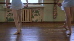 Two girls in ballet shoes do exercises during ballet class in frayed classroom stock footage