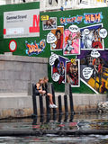 Two girls on a bank with graffiti in Copenhagen Royalty Free Stock Images