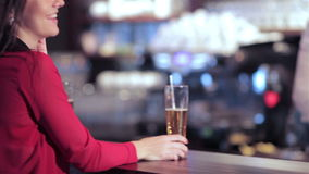 Two girls at the bar with a drink and the. Cheerful company of guys and girl celebrating at the bar. The company has a rest after work. Cheerful company relax stock footage
