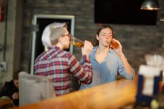 Two girls in a bar drinking beer. Indoors in a public place. stock image