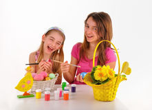 Two girls, basket with colored eggs, paint for coloring and a vase of flowers