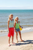 Two girls on the beach. Two girls standing on the beach on sunny day Royalty Free Stock Photos