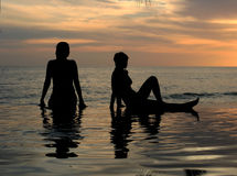 Two girls on the beach. Women and their reflections in a pool by the ocean Stock Image