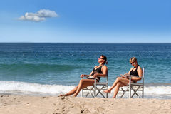 Two girls on the beach. 2 women reading on the beach Royalty Free Stock Images
