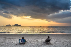 Two girls in beach chairs admiring the sunset at sea Stock Image