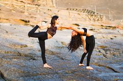 Two girls on the beach doing yoga at sunset. Lima Peru. royalty free stock photos