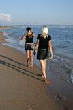 Two girls on a beach go afar Stock Photos
