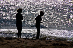 Two Girls on beach. Silhouette of two girls having fun on beach at sunset Royalty Free Stock Photo