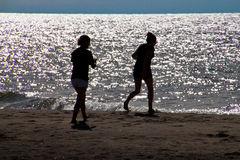 Two Girls on beach. Silhouette of two girls having fun on beach at sunset Royalty Free Stock Photography