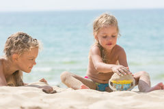 Two girls on beach on a sunny day, playing with sand and a bucket on a background of the sea Stock Photography